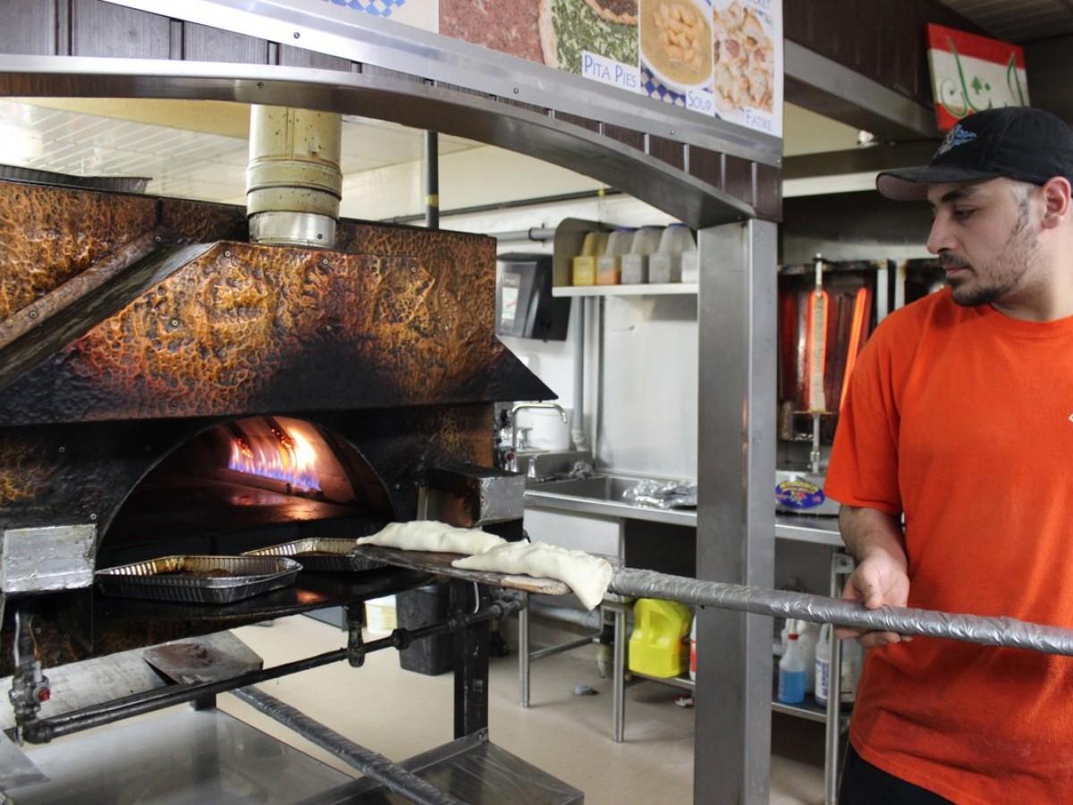 Winnipeg Middle Eastern food guide - Chef Rami Aboumrad of Baraka feeding pita pockets into the gas oven (PCG)