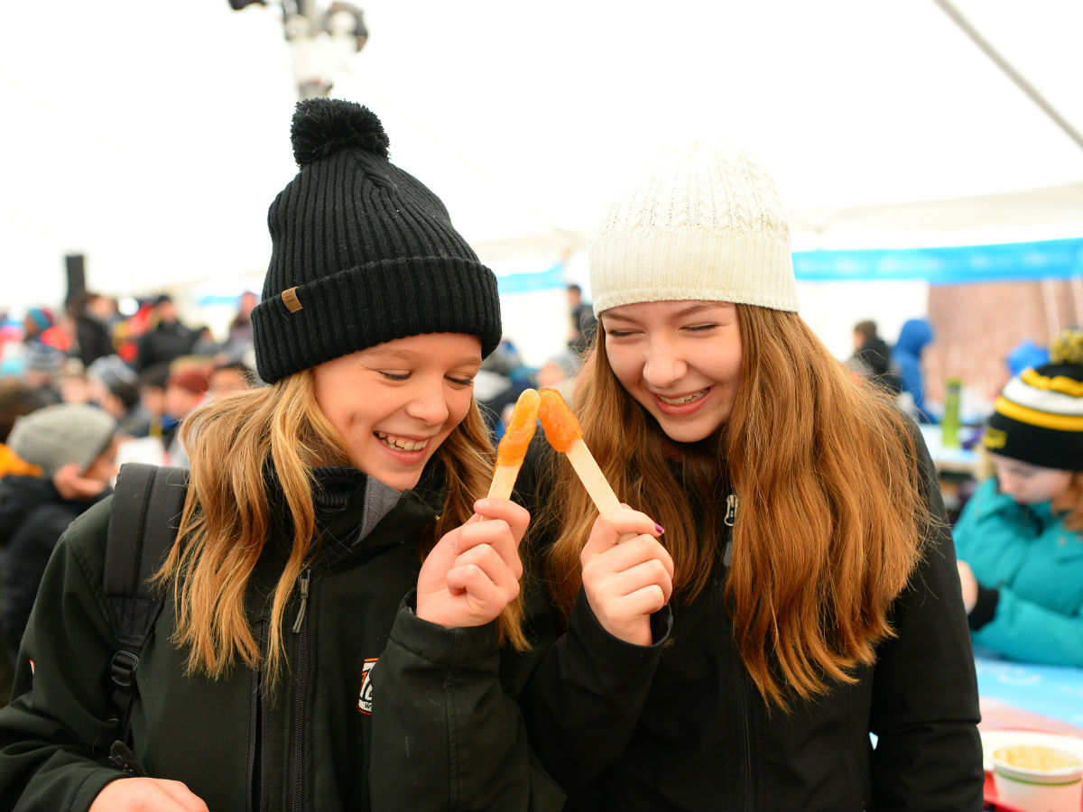 Mmm February: Food Festival Month - Two voyageurs enjoying some sticky maple treats