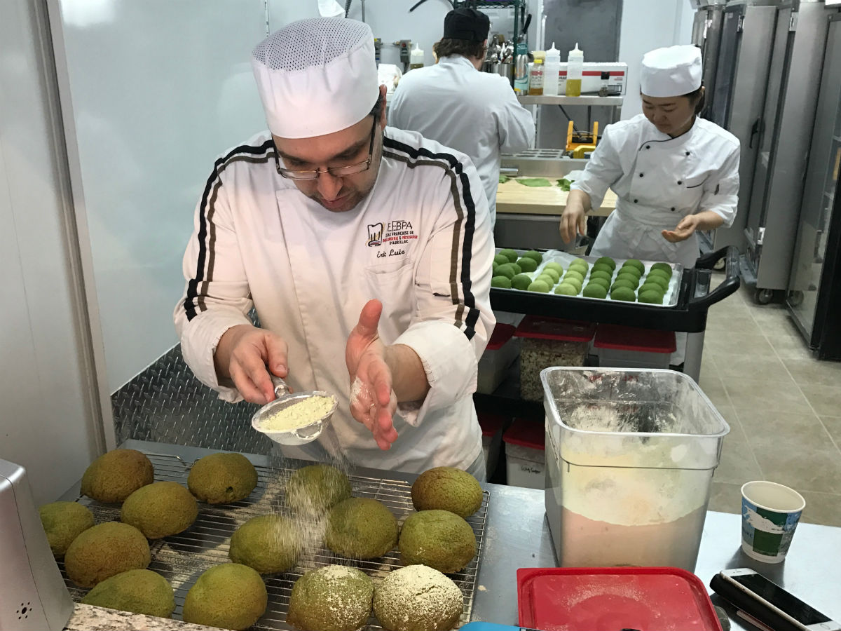 Winnipeg's newest bakery has customers clamouring for innovative pastries  - Head baker Eric Luiz dusting matcha brioche balls (PCG)