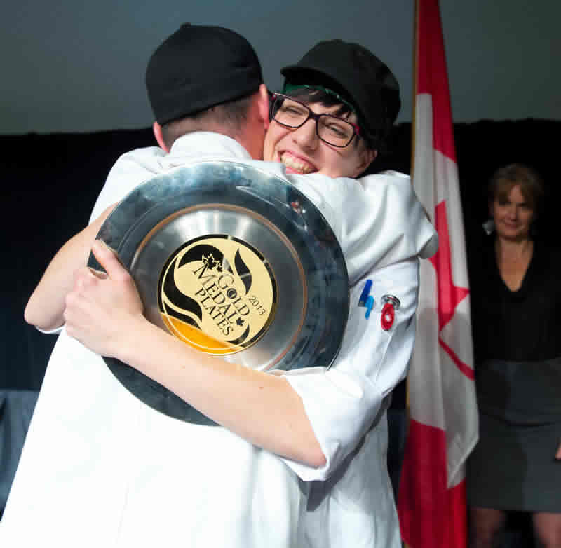 Chef Kelly Cattani of Elements Restaurant gets a celebratory hug from chef Ben Kramer after winning Gold Medal Plates in Winnipeg. (Photo by Dan Harper.)