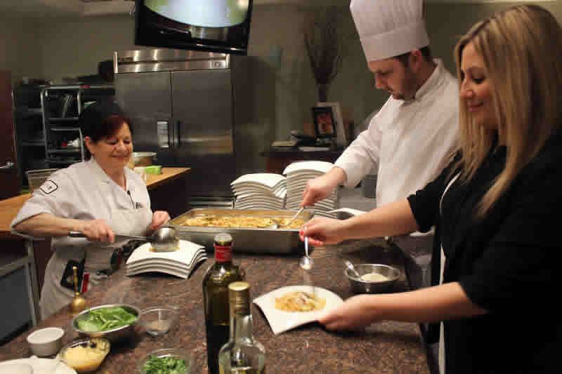 Instructor Anna Paganelli plates course during cooking class at De Luca's. (Photo by Robin Summerfield.)