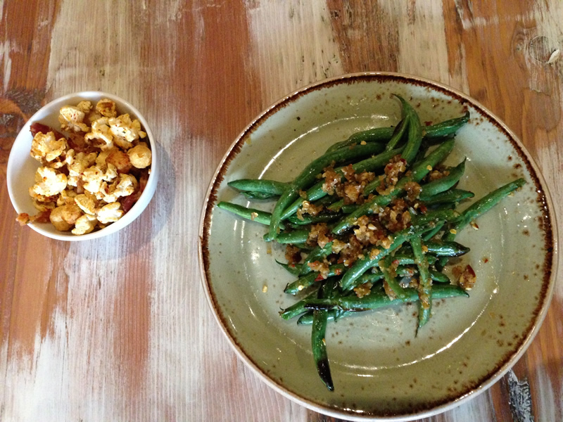 Fried green beans with arbol chiles, preserved mustard stems, and ginger along with a gochugaru-spiced popcorn (PCG)