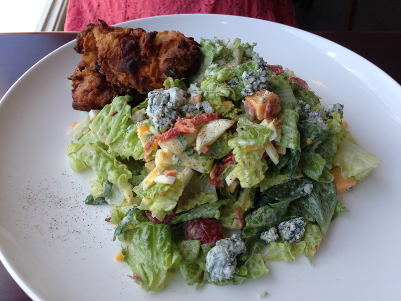 Buttermilk Fried Chicken Cobb with romaine, aged cheddar, bacon, egg, tomato, green onion, sun-dried tomato, blue cheese, ranch dressing (PCG)