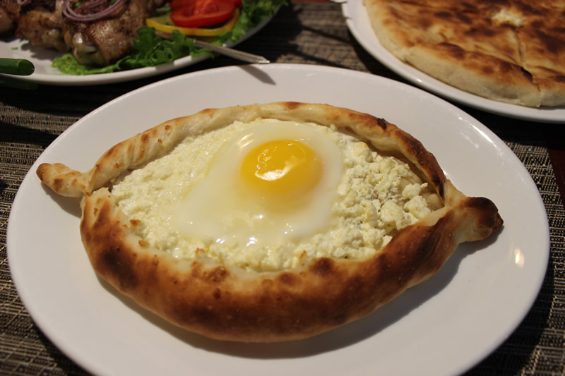 Khachapuri - Adjaruli ($14) Georgian flat bread baked with cheese and topped with an egg (PCG)